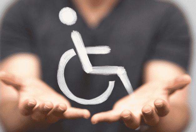 Symbole du handicap entre les deux mains d'un ostéopathe.